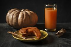 Baked pumpkin with cinnamon sticks, rustic spoon and a glass of juice stock photography