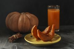 Baked pumpkin with cinnamon sticks, rustic spoon and a glass of juice stock images
