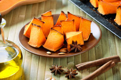 Baked pumpkin, cinnamon sticks, star anise and olive oil on a ki Royalty Free Stock Photography