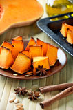 Baked pumpkin, cinnamon sticks, star anise and olive oil on a ki Stock Photography