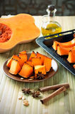 Baked pumpkin, cinnamon sticks, star anise and olive oil on a ki Royalty Free Stock Photos