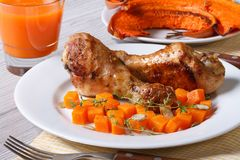 Baked pumpkin with fried chicken legs. Horizontal Stock Photo