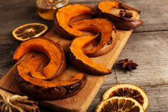 Baked pumpkin on the old wooden table and spices. Place for text, copy space stock photos