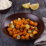 Baked pumpkin with onions, garlic and sage with boiled rice stock photography