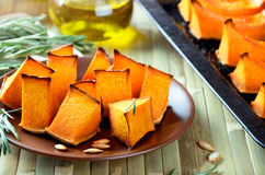 Baked pumpkin, rosemary and olive oil on a kitchen table closeup Stock Photography