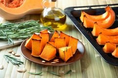 Baked pumpkin, rosemary and olive oil on a kitchen table horizon Stock Photos