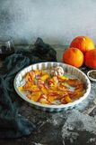 Baked pumpkin wrapped in bacon with rosemary and garlic. In a metallic baking pan stock image