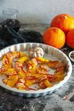 Baked pumpkin wrapped in bacon with rosemary and garlic. In a metallic baking pan royalty free stock photos