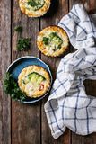 Baked quiche pie with greens. Baked homemade quiche pie in mini metal forms served with fresh greens with plate and kitchen towel on old plank wooden background Royalty Free Stock Image