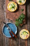 Baked quiche pie with greens. Baked homemade quiche pie in mini metal forms served with fresh greens, plate and cutlery on terracotta board on old plank wooden Stock Photo