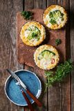 Baked quiche pie with greens. Baked homemade quiche pie in mini metal forms served with fresh greens, plate and cutlery on terracotta board on old plank wooden Royalty Free Stock Photo