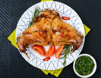 Baked rabbit legs on a plate on a black background. Royalty Free Stock Photo