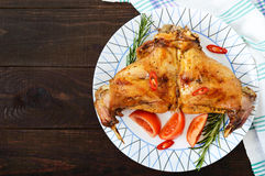 Baked rabbit legs on a plate on a dark wooden background. Dietary menu. Royalty Free Stock Photos