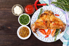 Baked rabbit legs on a plate and different sauces for meat on a dark wooden background. Royalty Free Stock Photography