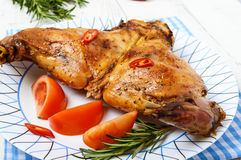 Baked rabbit legs on a plate. On a white wooden background Stock Photography