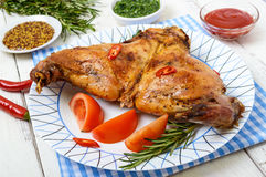 Baked rabbit legs on a plate Royalty Free Stock Images