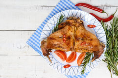 Baked rabbit legs on a plate on a white wooden background Royalty Free Stock Photo