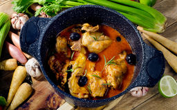 Baked rabbit legs. In tomato sauce with black olives and fresh herbs. Top view Stock Images