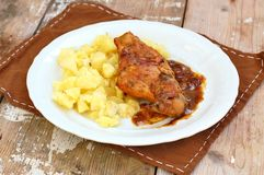 Baked rabbit with sauce and mashed potatoes on white plate on rustic table green cloth on rustic table Royalty Free Stock Photography