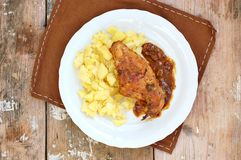 Baked rabbit with sauce and mashed potatoes on white plate on rustic table green cloth on rustic table Royalty Free Stock Photos