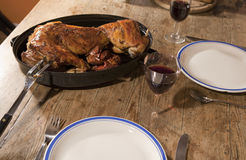 Baked rabbit. Served on an old table with wine Stock Photography