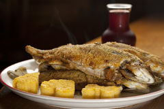 Baked rainbow trout with polenta. Delicious plate of rainbow baked trout with polenta and garlic Stock Image