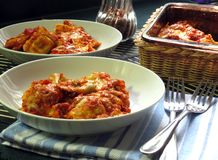 Baked Ravioli. Ravioli, baked with sauce and cheese, hot from the oven, served, and ready to eat stock image