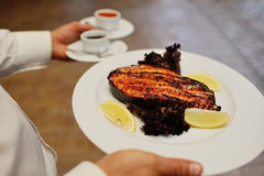 Baked red fish with a lemon. The waiter brings the red steak baked salmon Stock Photography