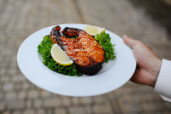 Baked red fish with a lemon. The waiter brings the red steak baked salmon Stock Images