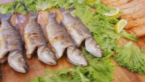 Baked red salmon with salad. Cooked fish fillets with greens and lemon on the table at the food festival. Baked red salmon with salad. Cooked fish fillets with stock video