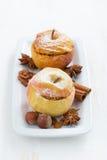 Baked rellenó manzanas en una placa en la tabla de madera blanca Foto de archivo libre de regalías