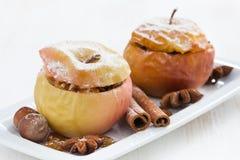 Baked rellenó manzanas en una placa en la tabla de madera blanca, primer Foto de archivo