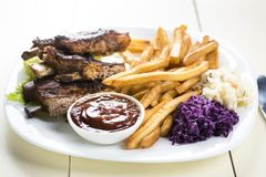Baked ribs and French fries and cabbage salad royalty free stock photo