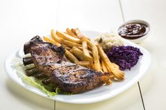 Baked ribs and French fries and cabbage salad stock photo