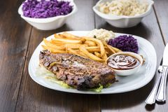 Baked ribs and French fries and cabbage salad stock images