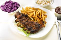 Baked ribs and French fries and cabbage salad royalty free stock photos
