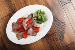 Baked roast beef with rucola. And bell pepper in a white oval plate. Wooden background Stock Images