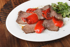 Baked roast beef with rucola. And bell pepper in a white oval plate. Wooden background Royalty Free Stock Photography