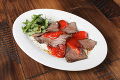 Baked roast beef with rucola and bell pepper. In a white oval plate. Wooden background Stock Photos