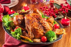 Baked or roasted whole chicken on Christmas table stock image