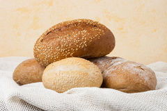 Baked rolls and bread on table. Baked rolls with sesame seeds and bread on table napkin Royalty Free Stock Photography
