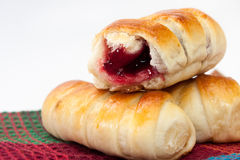 Baked rolls with cream cherry on the kitchen tablecloth Stock Image