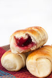 Baked rolls with cream cherry on the kitchen tablecloth Stock Photo