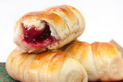 Baked rolls with cream cherry on the kitchen tablecloth Royalty Free Stock Photos
