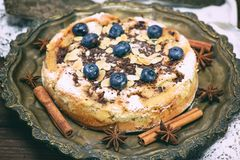 Baked round cake with blueberry berries on a copper plate Stock Photo