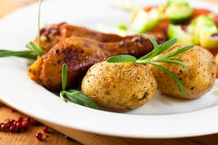 Baked rustic potatoes and roast chicken stock image