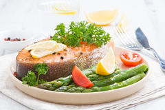 Baked salmon with asparagus and lemon on plate. Close-up Stock Photos