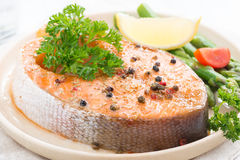 Baked salmon with asparagus and lemon on plate, close-up Stock Images