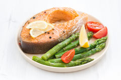 Baked salmon with asparagus and lemon. On white wooden table Royalty Free Stock Image