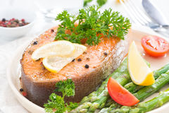 Baked salmon with asparagus, parsley and lemon, close-up Stock Images